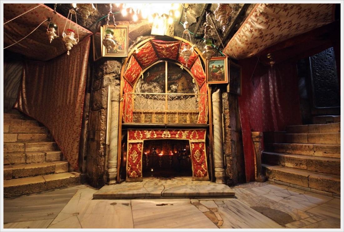 wnętrze groty narodzenia, w centralnym punkcie znajduje się gwiazda wskazująca miejsce narodzenia Jezusa, do groty prowadzą schody