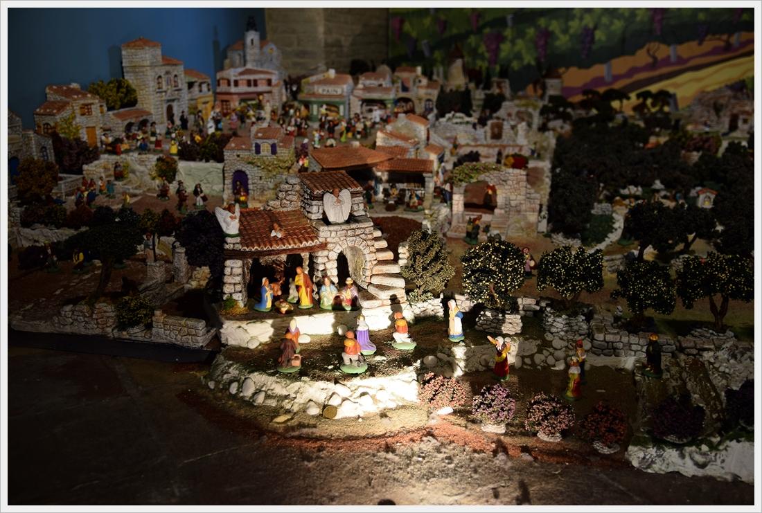 miasteczko Betlejem z licznymi zabudowaniami, na pierwszym planie Maryja z Józefem oraz dzieciątkiem poniżej pasterze