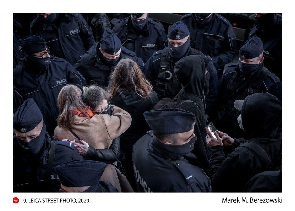 fotografia przedstawiająca tłum policjantów, pośrodku niego dwie kobiety przytulają się