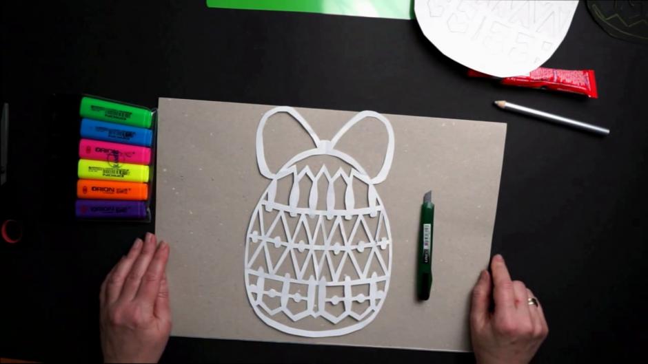 dłonie wycinające pisankę z białego papieru