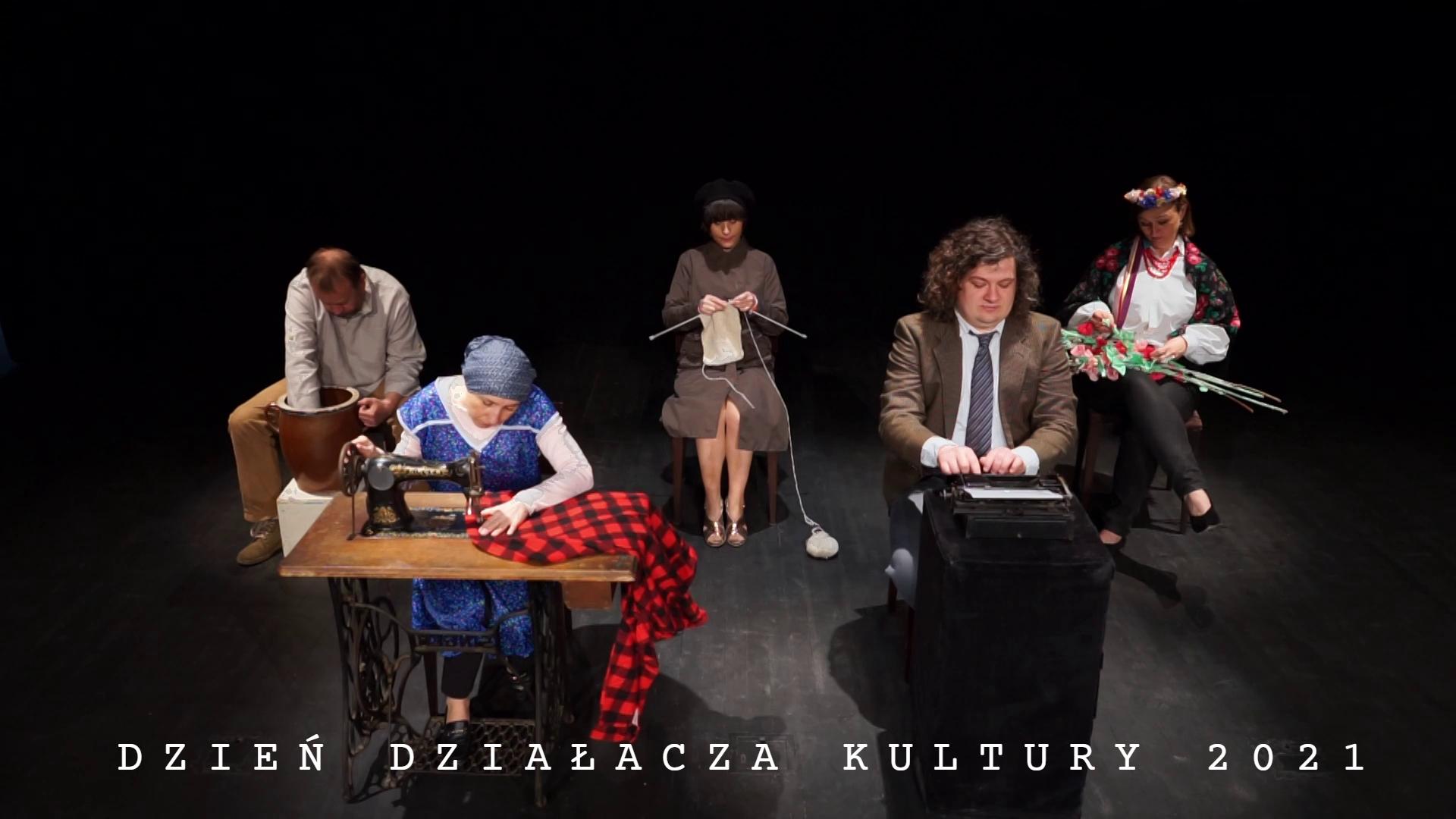 Pięć postaci w strojach a la PRL pracuje na ciemnym tle sceny ŚOK