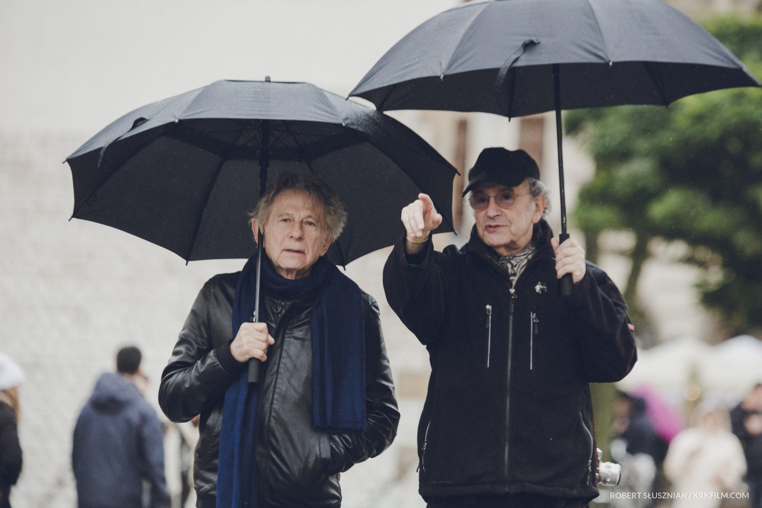 Reżyser Polański i fotograf Horowitz na drodze z parasolami